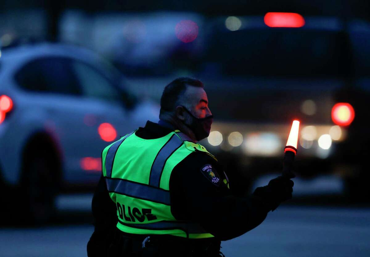 Conroe Police officers guide traffic into the Woodforest Bank Stadium parking lot to Montgomery County's third mass COVID-19 vaccination site, Friday, Feb. 5, 2020, in Shenandoah.