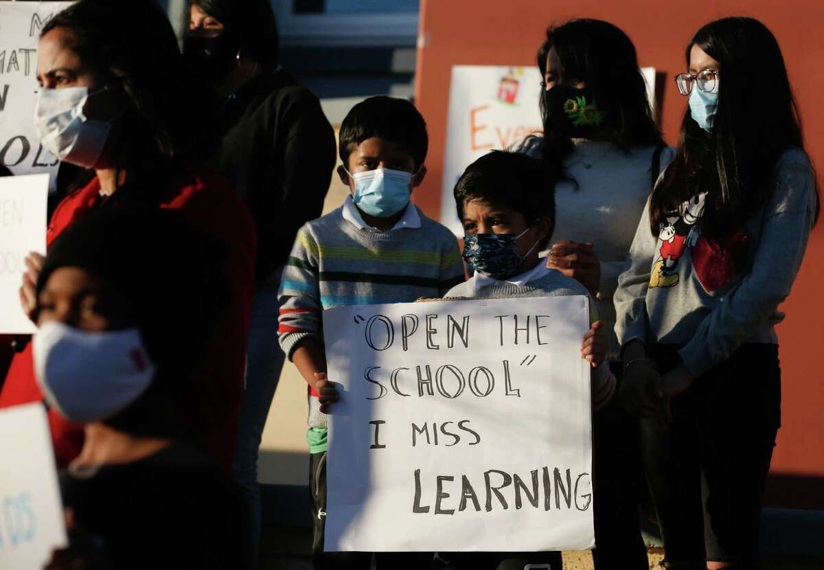 Brothers Daniel Martinez, 9, (L) and Brian ,7, and hold a sign as families and city officials including Mayor London Breed, attend a press conference with the organization Decreasing the Distance to support the reopening of San Francisco's public schools on Thursday, February 4, 2021.