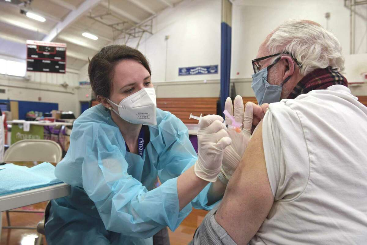 Bridget Bethray RN, with RVNAhealth administers a COVID-19 vaccine to Sherwin Gorenstein, of Ridgefield, in the RVNA clinic in the Yanity Gym, on Thursday morning in Ridgefield.