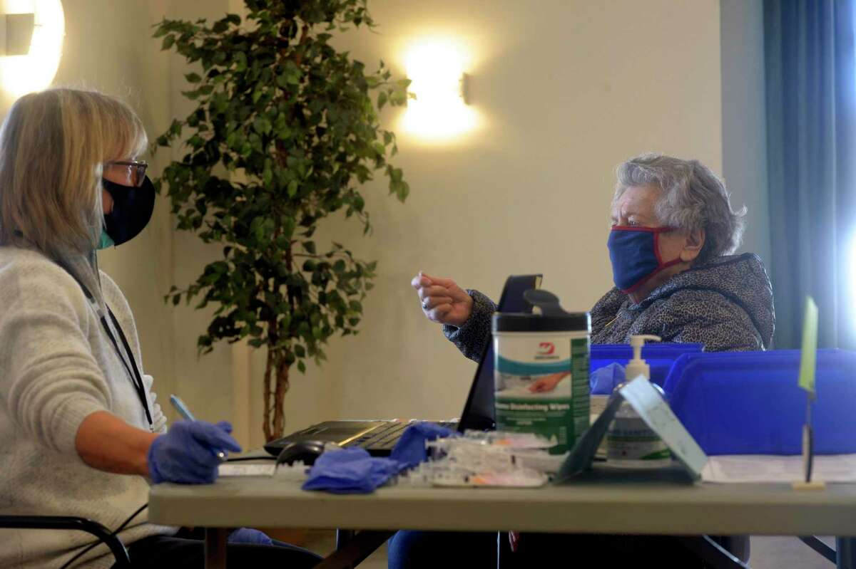Elisabeth Mohr, right, gives information to volunteer Chris Staskiewicz RN at the Brookfield COVID-19 vaccination clinic held in the Brookfield Senior Center on Thursday, February 4, 2021, in Brookfield, Conn.