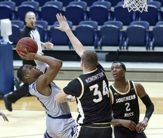 Rice Owls guard Quincy Olivari (4) goes up the basket against Southern Miss Golden Eagles forward Artur Konontsuk (34) during the second half of an NCAA men's basketball game at Tudor Field House in Houston, Friday, Feb. 5. Photo: Karen Warren, Staff Photographer / © 2021 Houston Chronicle