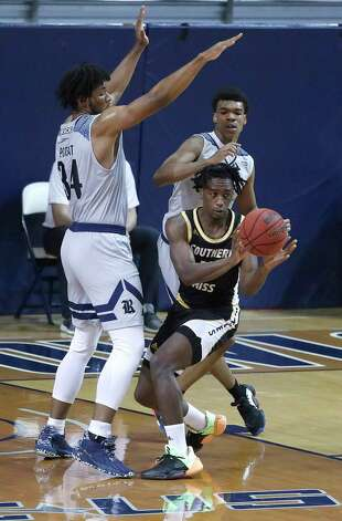 Southern Miss Golden Eagles guard Tae Hardy (10) looks to pass the ball against the defense of Rice Owls forwards Mylyjael Poteat (34) and Cameron Sheffield (5) during the second half of an NCAA men's basketball game at Tudor Field House in Houston, Friday, Feb. 5. Photo: Karen Warren, Staff Photographer / © 2021 Houston Chronicle