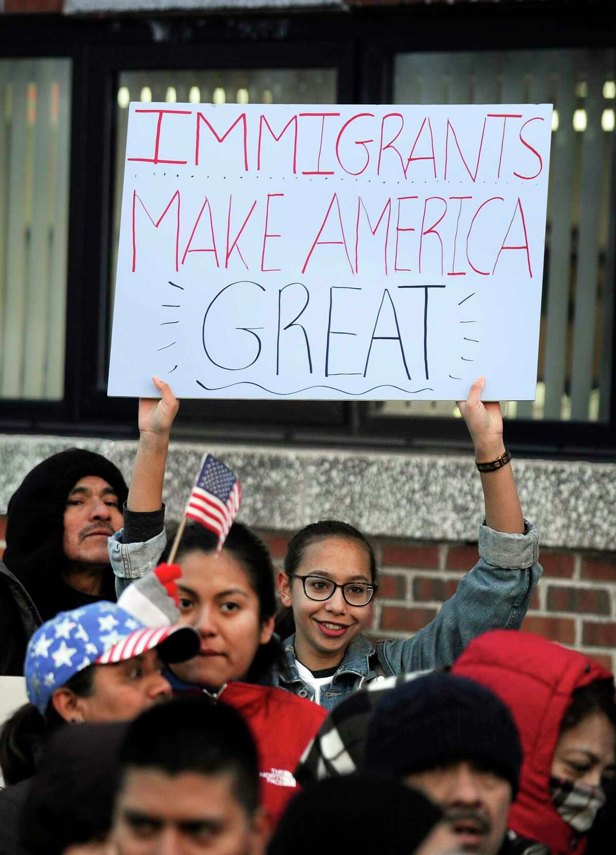 """Gabby Perez, 17, of Danbury, holds a """"Immigrants make America great"""" sign at a """"Day without immigrants"""" rally at the Danbury City Hall Thursday, February 16, 2017."""