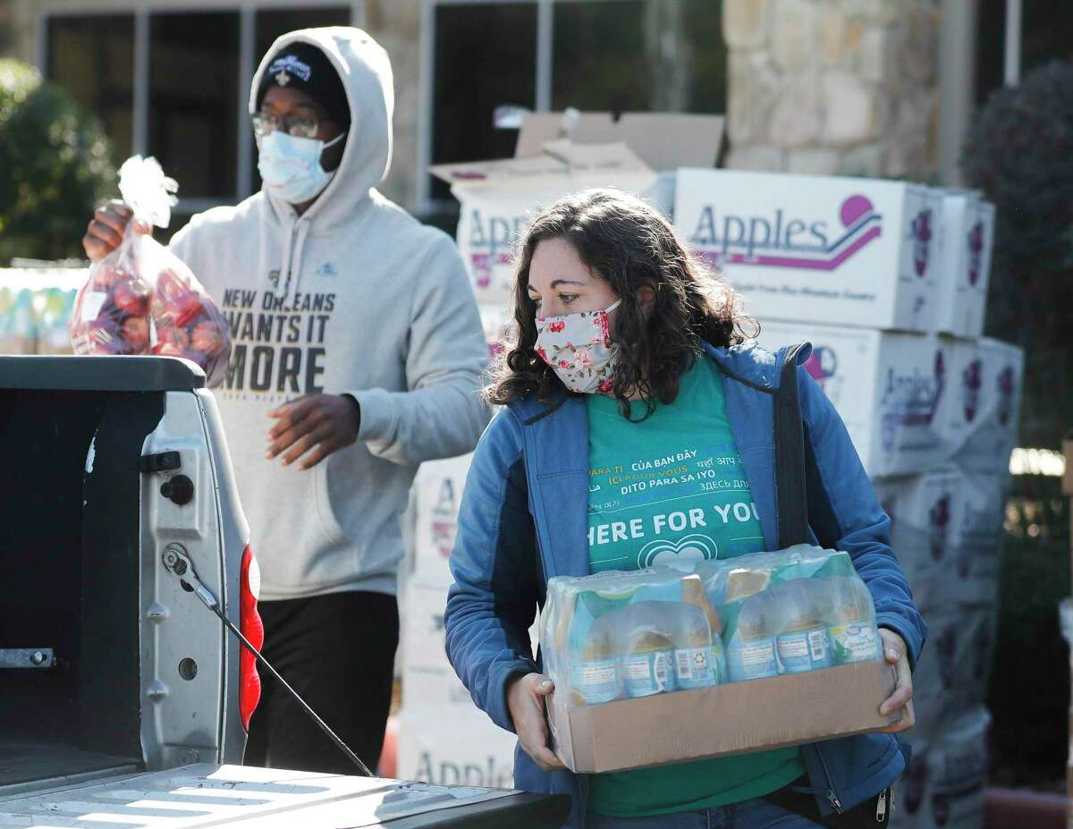 Whitney Vasquez items into a truck as volunteers help distribute food for 200 families as part of YMCA's Mobile Market Food Drive in partnership with the Montgomery County Food Bank at Generations Church, Saturday, Jan. 9, 2021.