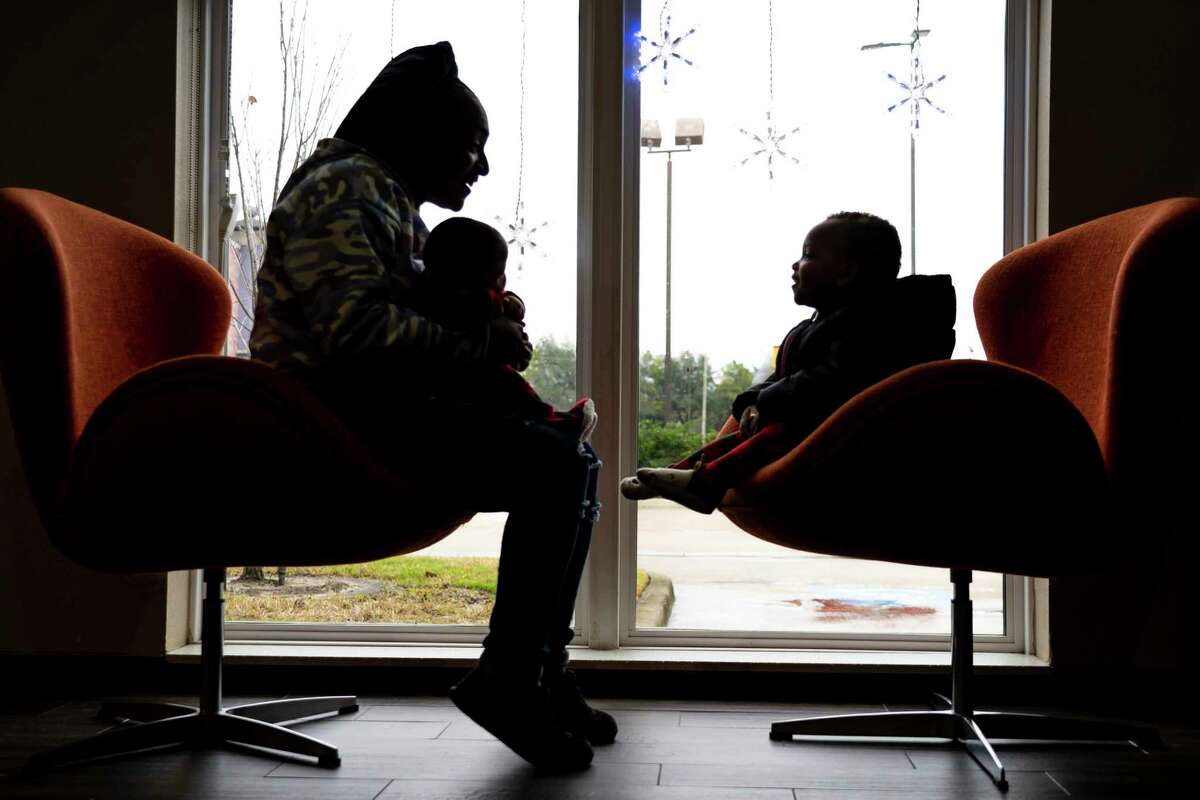 ShyMesha Hawkins sits with her two-year-old son, Sir'Bastyn, and three-month-old daughter, Sir'Enity, at the hotel where they have been staying while waiting to move into a new apartment, Tuesday, Dec. 15, 2020, in Houston. Hawkins has been struggling to pay her bills during the pandemic, returning to her job at MOD Pizza just two weeks after delivering Sir'Enity earlier this year.