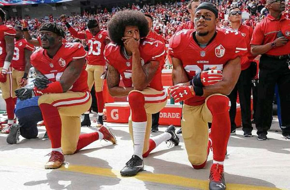 Eli Harold, Colin Kaepernick and Eric Reid of the 49ers kneel during the national anthem before a game against the Cowboys on Oct. 2, 2016 at Levi's Stadium, in Santa Clara, Calif.