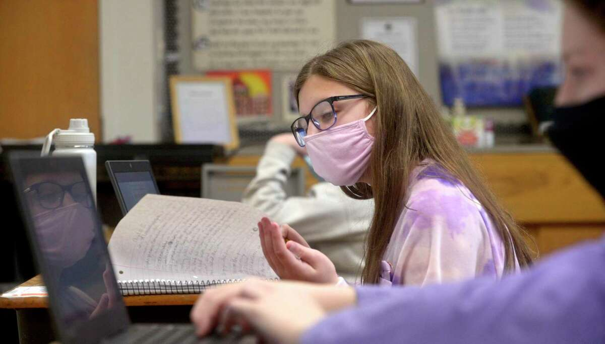 Gianna Alfano, of Danbury, age 11, of Danbury, looks at her notes during a sixth grade science class at St Joseph School. Catholic schools like St Joseph have been able to stay open five days a week for all students during the coronavirus pandemic. Friday, February 5, 2021, in Danbury, Conn.