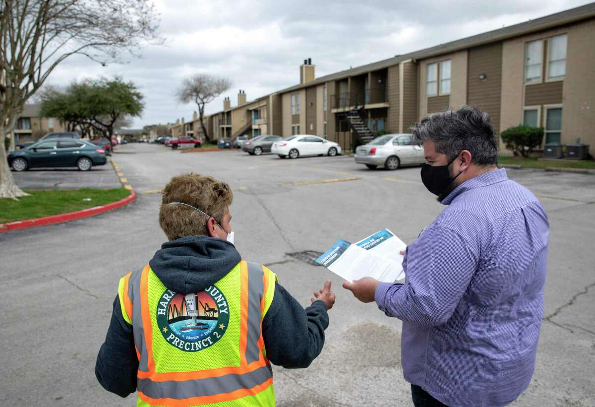 Francisco Castillo, left, and Selina Valdez distribute information about tenants' rights as they relate to eviction proceedings and the COVID-19 pandemic Thursday, Feb. 4, 2021, at Timber Ridge Apartments in Houston.