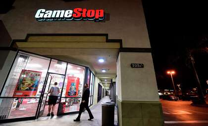 People enter a GameStop store in Alhambra, California on January 27, 2021. In response to stock market volatility surrounding companies such as GameStop, Greenwich-based brokerage Interactive Brokers Group announced what would turn out to be short-lived trading restrictions affecting stocks and options of GameStop and several other companies.