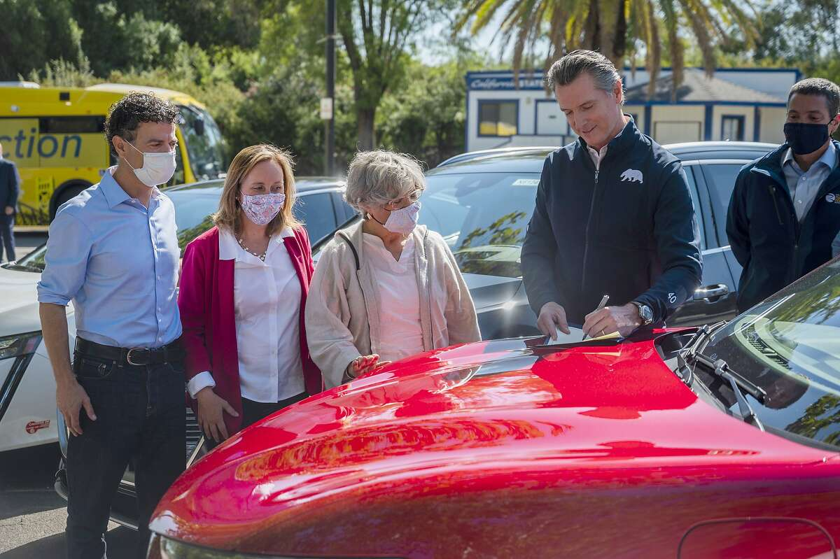 On the hood of an electric car, California Gov. Gavin Newsom signs an executive order last year requiring all new passenger vehicles sold in the state to be zero-emission by 2035.