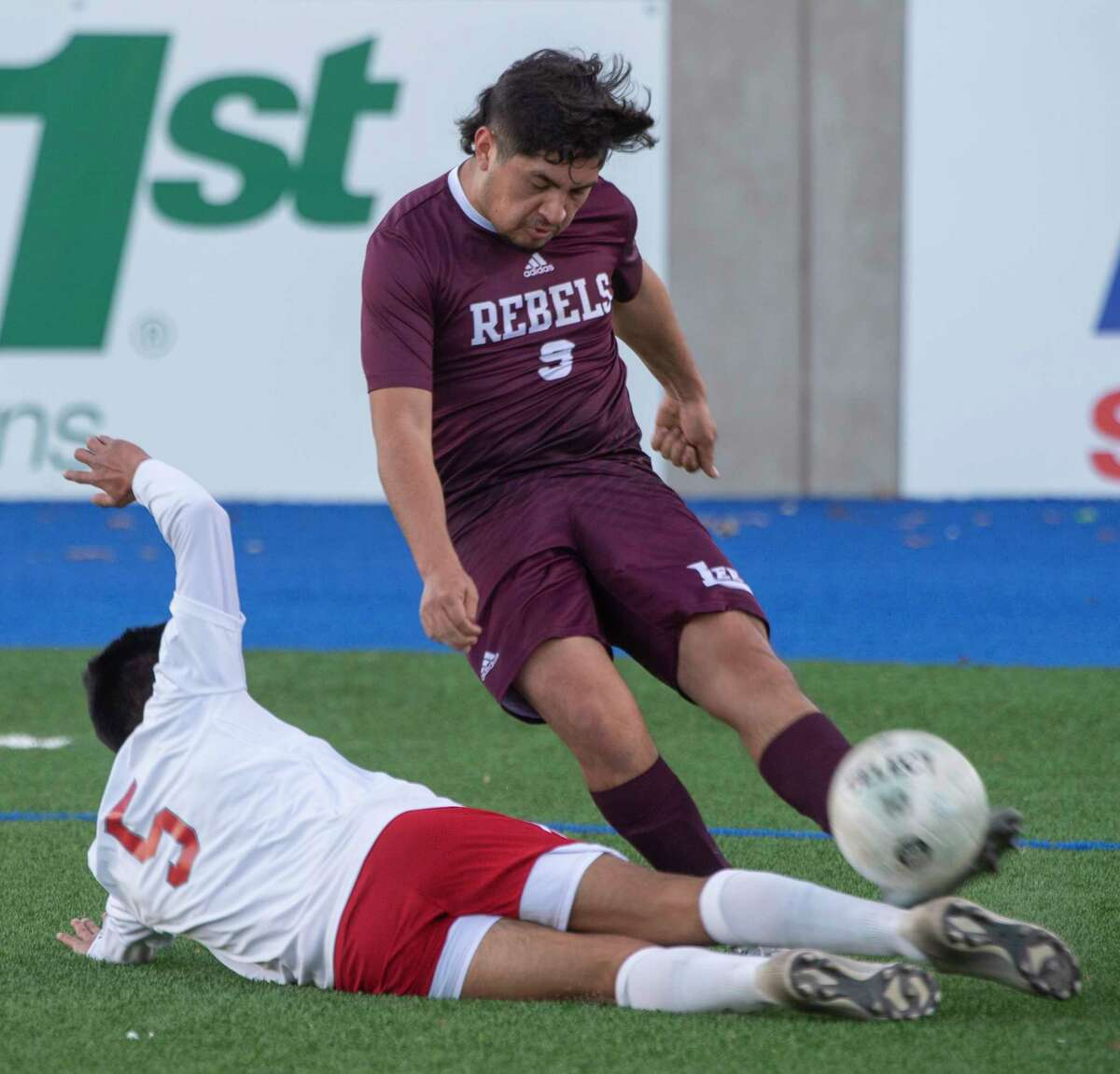 Lee High's Christian Olivias clears the ball as Odessa High's Jr Mora slides in trying to knock the ball away 02/05/2021 at Grande Communications Stadium Tim Fischer/Reporter-Telegram
