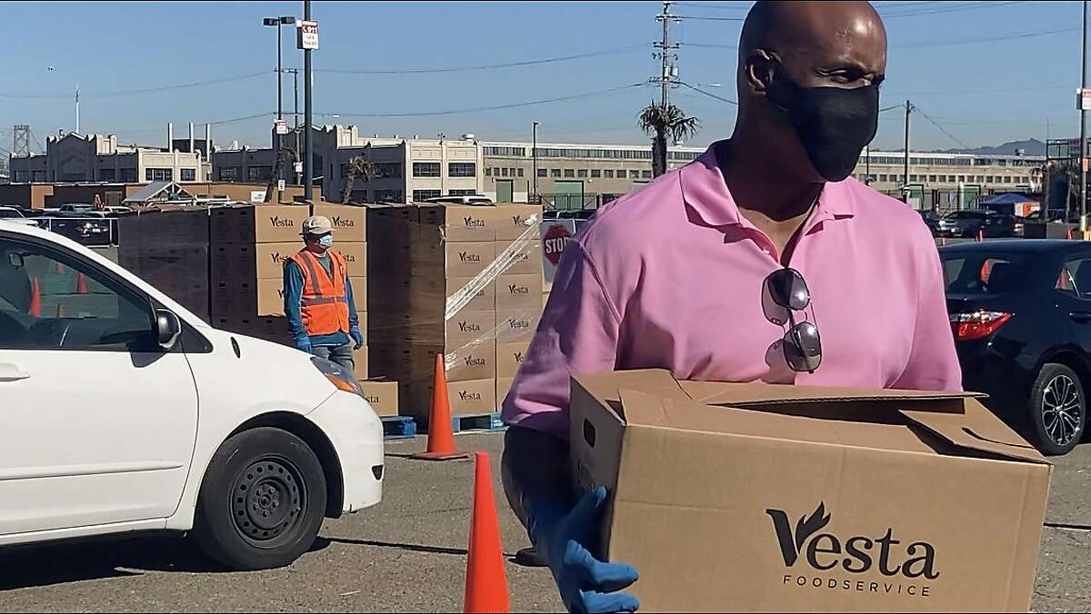 Barry Bonds places boxes of food into vehicles during a Marin-San Francisco Food Bank distribution in Lot A near Oracle Park on Jan. 5, 2021.