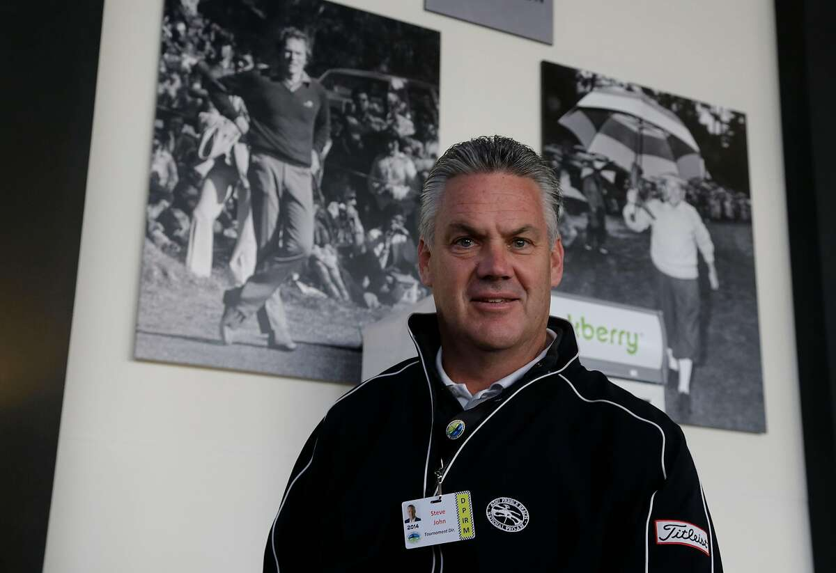 Steve John, CEO of the Monterey Peninsula Foundation and tournament director of the AT&T Pebble Beach Pro-Am, poses beneath photographs of Clint Eastwood (left) and Bing Crosby (right) on Feb. 7, 2014. John was choking on a piece of cheese at a volunteer party when Eastwood gave him the Heimlech maneuver two nights earlier.