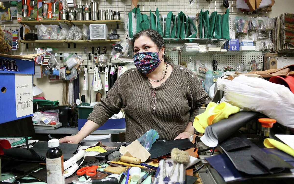 Tania Alejandra, owner of Texas Luxury Goods, works on organizing her down-sized workspace in Houston on Friday, Feb. 5, 2021. Alejandra's landlord let her downsize her space to save money.