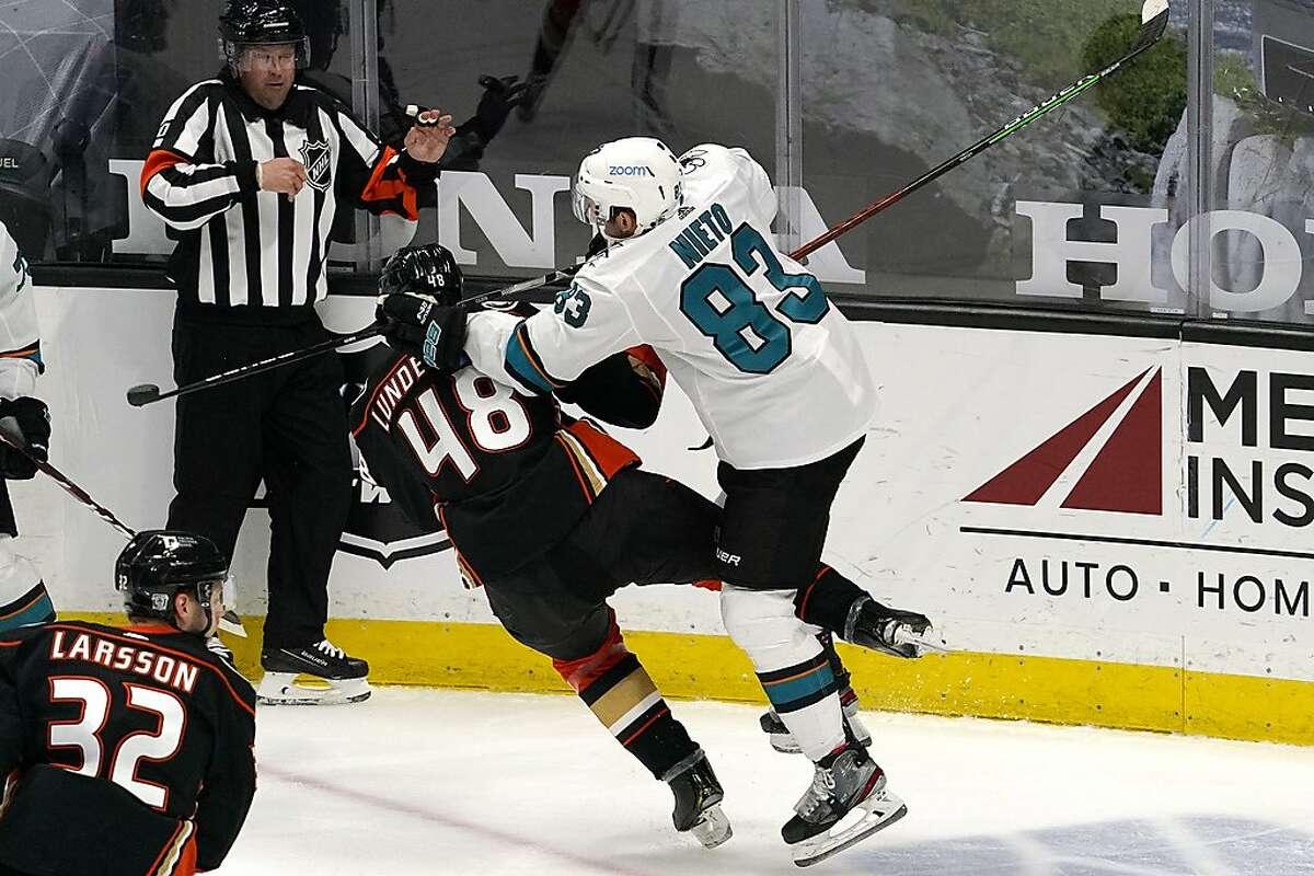 Sharks left wing Matt Nieto, a California native, puts a hit on Ducks center Isac Lundestrom.