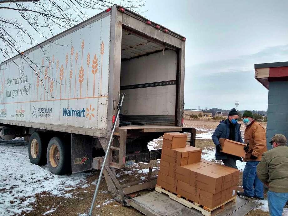 Senior Center volunteers help unload the Feeding America truck this week. (Courtesy photo)