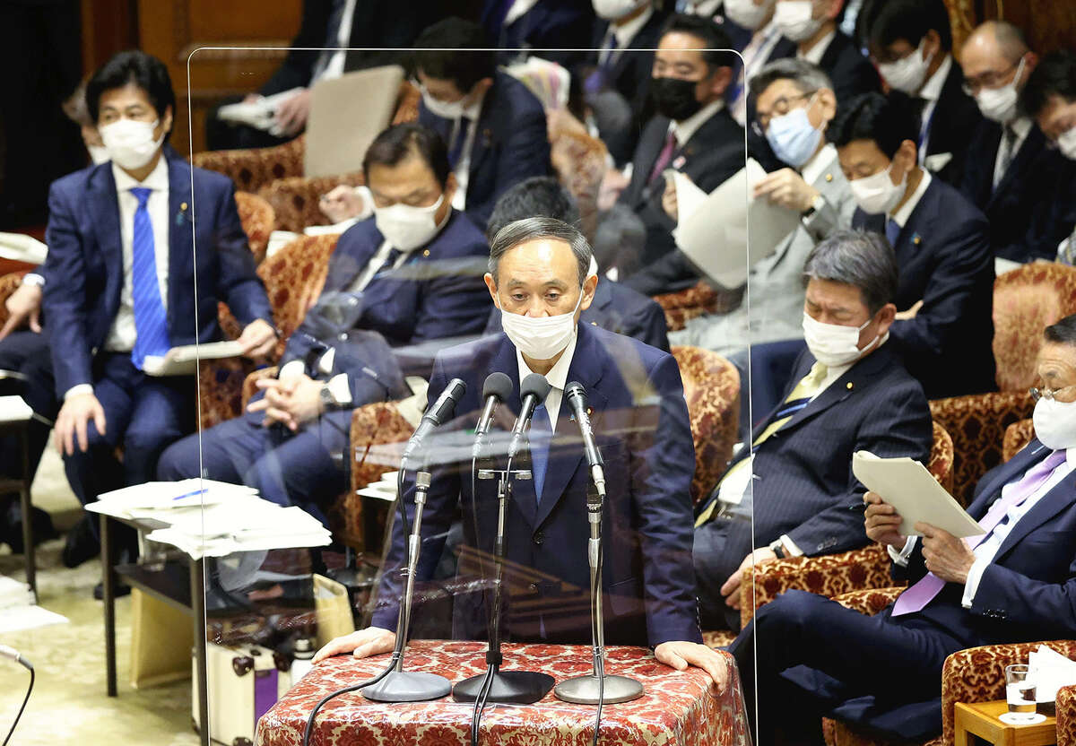 Prime Minister Yoshihide Suga speaks behind an acrylic panel during a House of Representatives Budget Committee session in the Diet building on Jan. 25.
