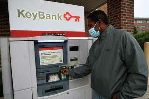 Kenneth Moss uses the ATM at the Key Bank on Canal Street in Stamford, Conn. on Monday, October 12, 2020. Moss' friend Leon Standly, a Pacific House Shelter resident, helped Moss get a hassle free account at the bank after developing a relationship with a bank manager.