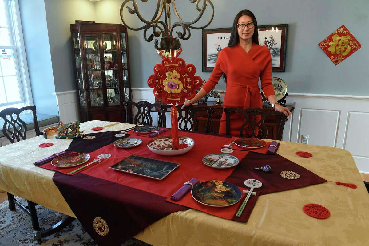 Wei Qin stands next to her elaborate traditional banquet table setting for the upcoming Chinese New Year holiday on Friday, Feb. 5, 2021 in Schenectady, N.Y. The holiday starts on begins Friday, Feb. 12. (Lori Van Buren/Times Union)