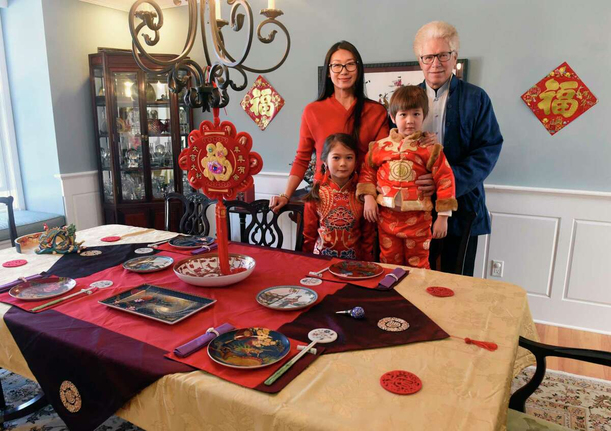 Wei Qin stands with her husband William Cooney, daughter Angelica Cooney, 7, and son Alexander, 3, next to their elaborate traditional banquet table setting for the upcoming Chinese New Year holiday on Friday, Feb. 5, 2021 in Schenectady, N.Y. The holiday starts on begins Friday, Feb. 12. (Lori Van Buren/Times Union)