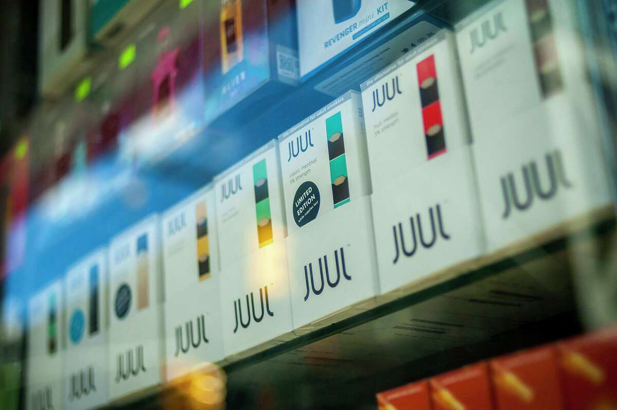 A selection of Juul brand vaping supplies on display in the window of a vaping store in New York.