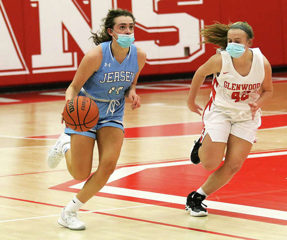 Jersey's Chloe White checks the clock as she pushes the ball upcourt while Glenwood's Erin Mansfield defends in the final seconds of the first half on Friday night in Chatham. Photo: Greg Shashack / The Telegraph