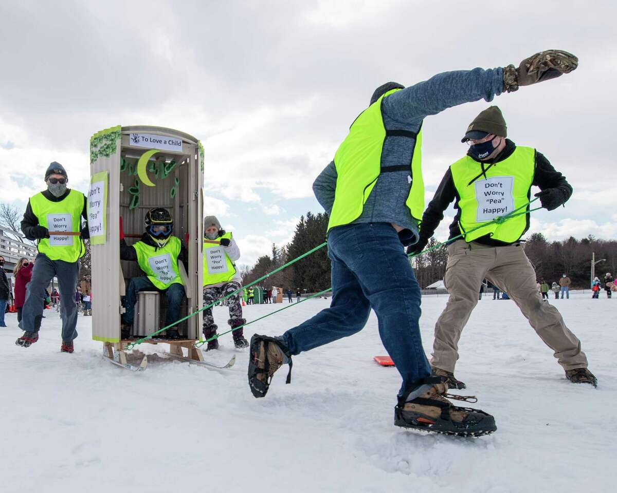 """The """"Pea Happy"""" outhouse racing team competes at the Clifton Commons during the Clifton Park Winterfest on Saturday, Feb. 6, 2021. The """"Pea Happy"""" team won the race that featured six outhouses (Jim Franco/special to the Times Union.)"""