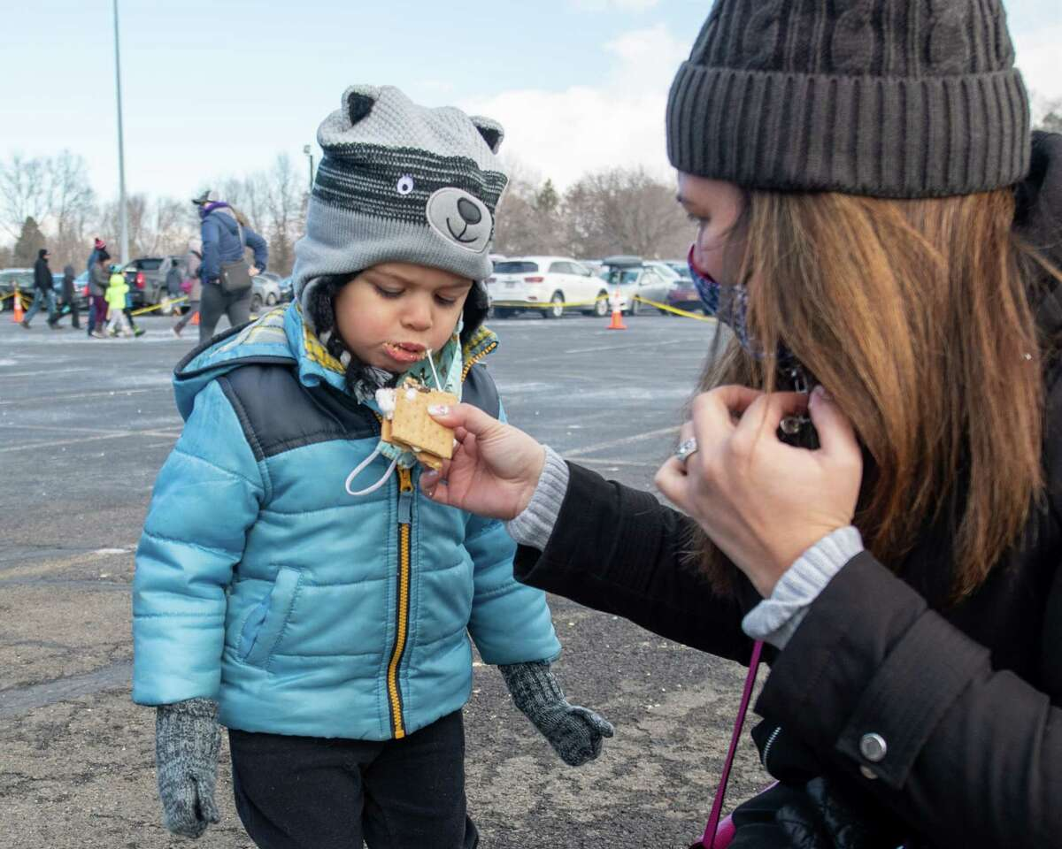 Catey Brewer feeds Chase Brewer a s'more at the Clifton Commons during the Clifton Park Winterfest on Saturday, Feb. 6, 2021. (Jim Franco/special to the Times Union.)