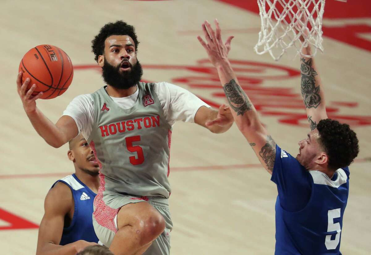 Houston guard Cameron Tyson (5) takes the ball to the basket against Our Lady of the Lake forward Ruben Monzon during the first half on a NCAA basketball game at Fertitta Center Saturday, Feb. 6, 2021, at Fertitta Center in Houston.