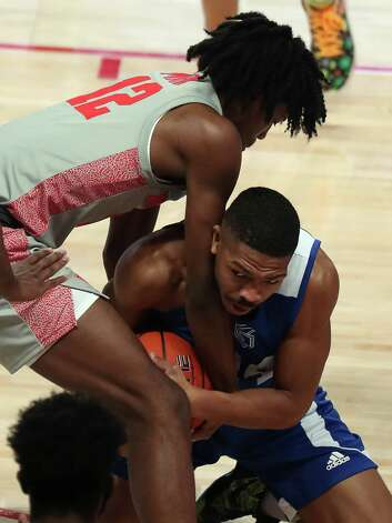 Houston guard Tramon Mark (12) and Our Lady of the Lake guard Ethan White (24) fight for a loose ball during the first half on an NCAA basketball game at Fertitta Center Saturday, Feb. 6, 2021, at Fertitta Center in Houston. Photo: Brett Coomer, Staff Photographer / © 2021 Houston Chronicle