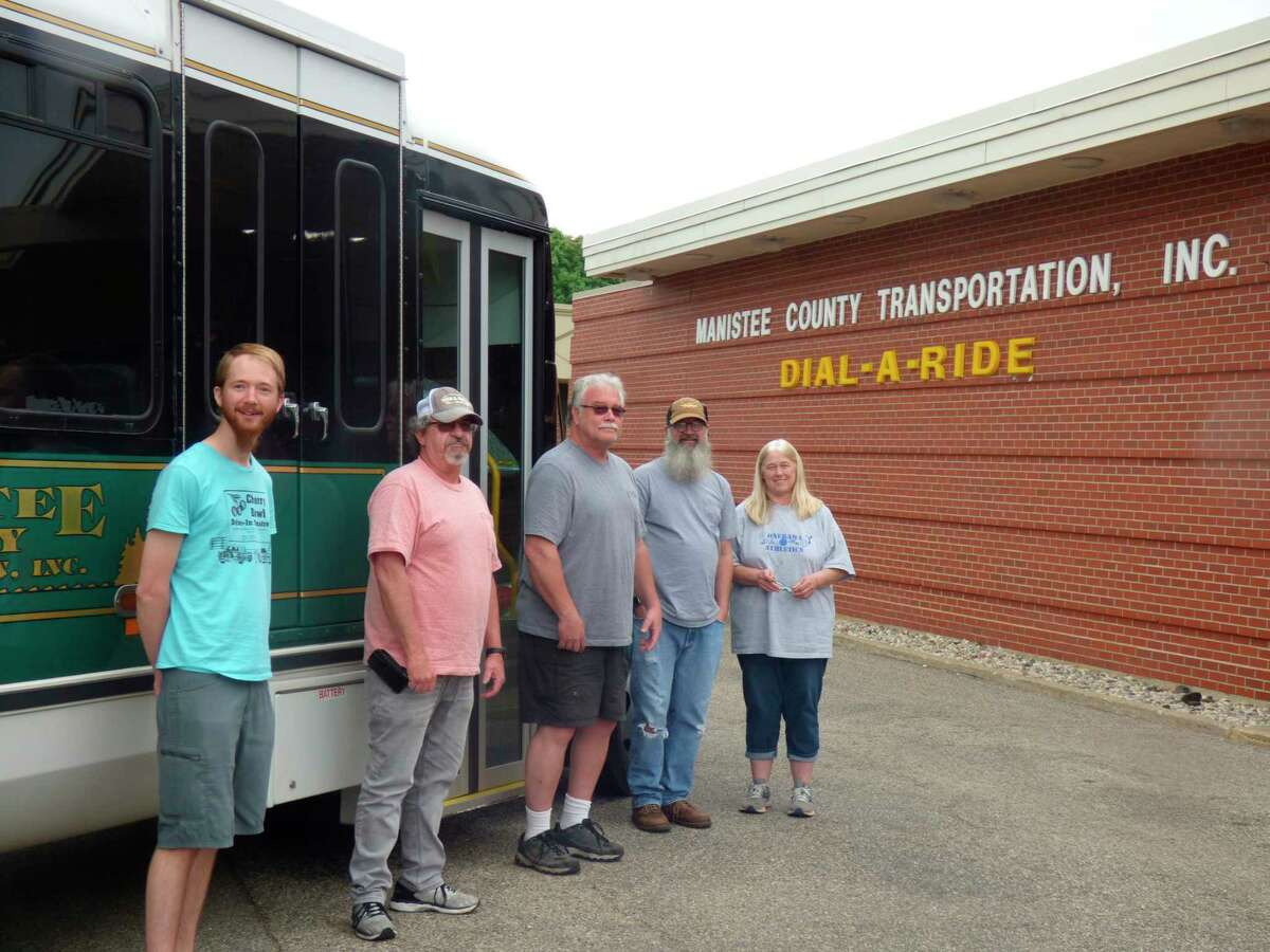 Dial-A-Ride drivers (from left) Curtis Gauthier, Larry Budde, Joe Fisk and Richard Morehouse along with operations manager Denise Peters, have continued to provide public transportation services during the pandemic. (File photo)A Dial-A-Ride driver collects items from a food pantry to deliver for those isolated at home. (File photo)