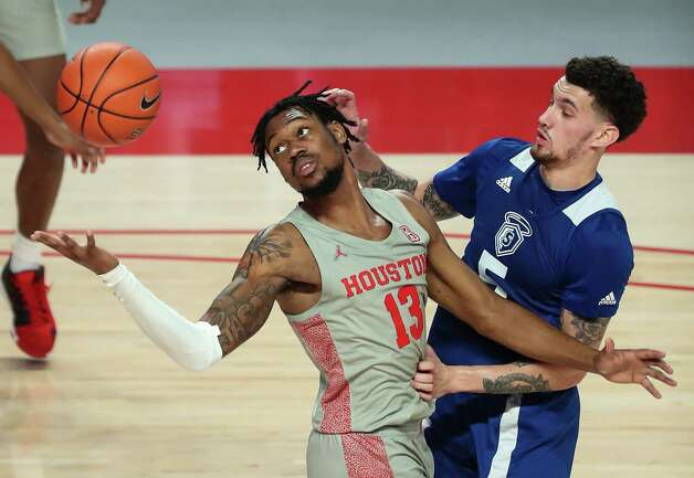 Houston forward J'Wan Roberts (13) goes after a loose ball against Our Lady of the Lake forward Ruben Monzon (5) during the second half on a NCAA basketball game at Fertitta Center Saturday, Feb. 6, 2021, at Fertitta Center in Houston. UH won the game 112-46. Photo: Brett Coomer, Staff Photographer / © 2021 Houston Chronicle