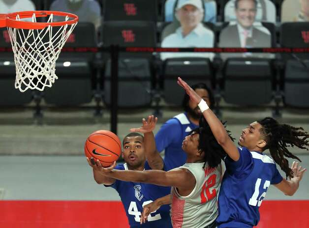 Houston guard Tramon Mark, center, drives to the basket against Our Lady of the Lakeguard Cameron Fields (42) and guard Xavier Woodington, right, during the second half on a NCAA basketball game at Fertitta Center Saturday, Feb. 6, 2021, at Fertitta Center in Houston. UH won the game 112-46. Photo: Brett Coomer, Staff Photographer / © 2021 Houston Chronicle