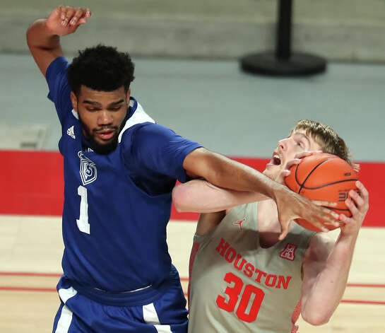 Our Lady of the Lake forward Jordan Embry (1) fouls Houston center Caleb Broodo (30) as he goes up for a shot during the second half on a NCAA basketball game at Fertitta Center Saturday, Feb. 6, 2021, at Fertitta Center in Houston. UH won the game 112-46. Photo: Brett Coomer, Staff Photographer / © 2021 Houston Chronicle
