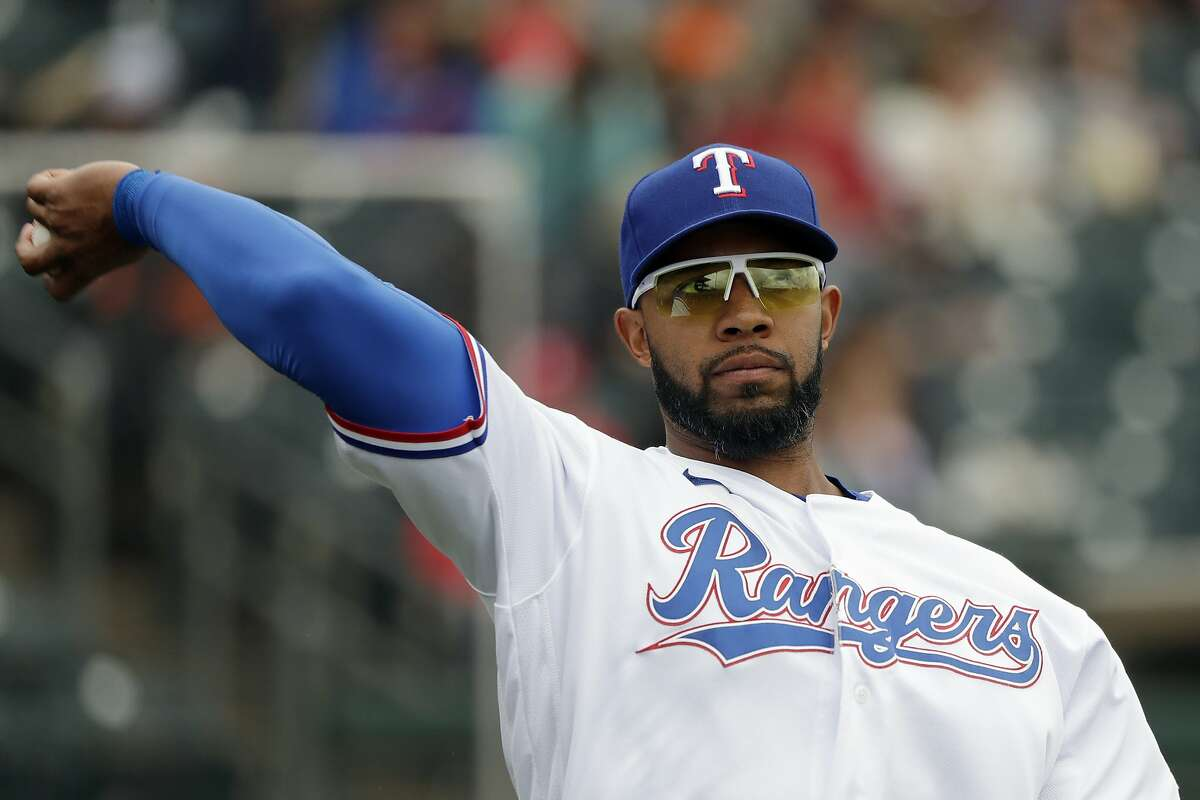 FILE - In this March 11, 2020, file photo, Texas Rangers' Elvis Andrus tosses a ball before a spring training baseball game against the San Francisco Giants in Surprise, Ariz. The Rangers traded Andrus to the Oakland Athletics on Saturday, Feb. 6, 2021. Texas is sending the 32-year-old Andrus, catcher Aramis Garcia and $13.5 million to the A's for designated hitter Khris Davis, along with catcher Jonah Heim and right-hander Dane Acker. (AP Photo/Elaine Thompson, File)