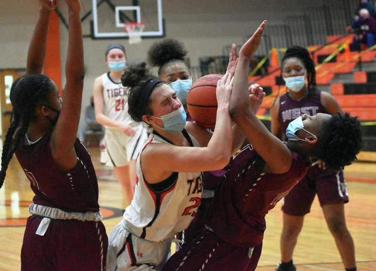 Edwardsville junior Macy Silvey collides with a Belleville West defender as she attempts to drive to the basket in the first quarter.