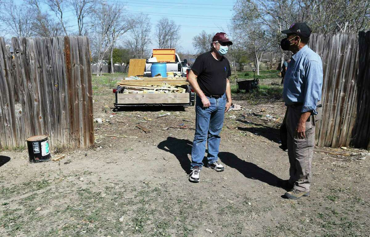 Landscape architect and historian Everett Fly (right) and retired Air Force Maj. J. Michael Wright chat on the grounds of the Hockley Cemetery as contractors move the fences of residents whose property overlapped to the cemetery that Fly and Wright discovered in a Northeast Side neighborhood on Thursday, Feb. 4, 2021.