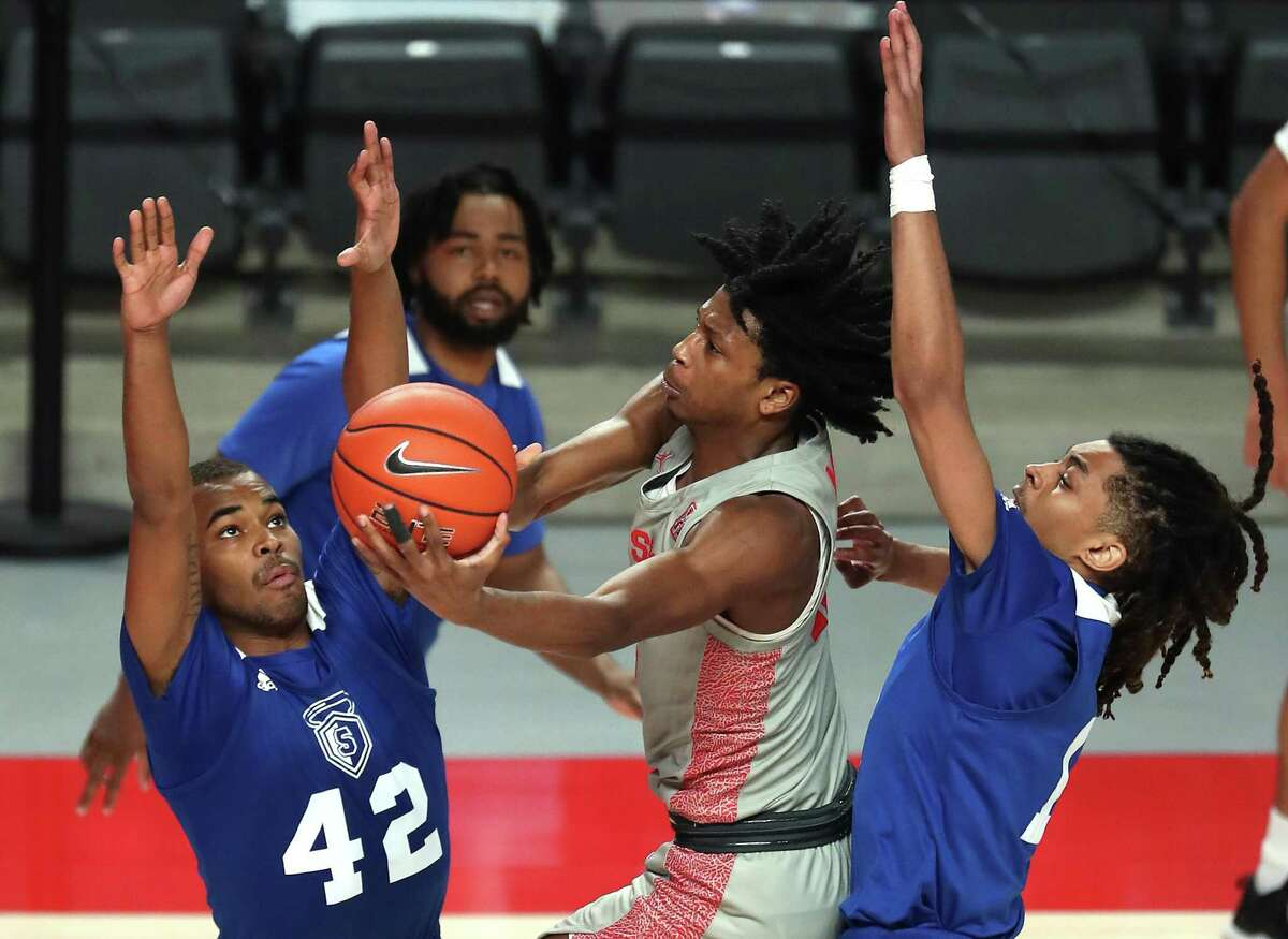 Houston guard Tramon Mark, center, drives to the basket against Our Lady of the Lakeguard Cameron Fields (42) and guard Xavier Woodington, right, during the second half on a NCAA basketball game at Fertitta Center Saturday, Feb. 6, 2021, in Houston. UH won the game 112-46.