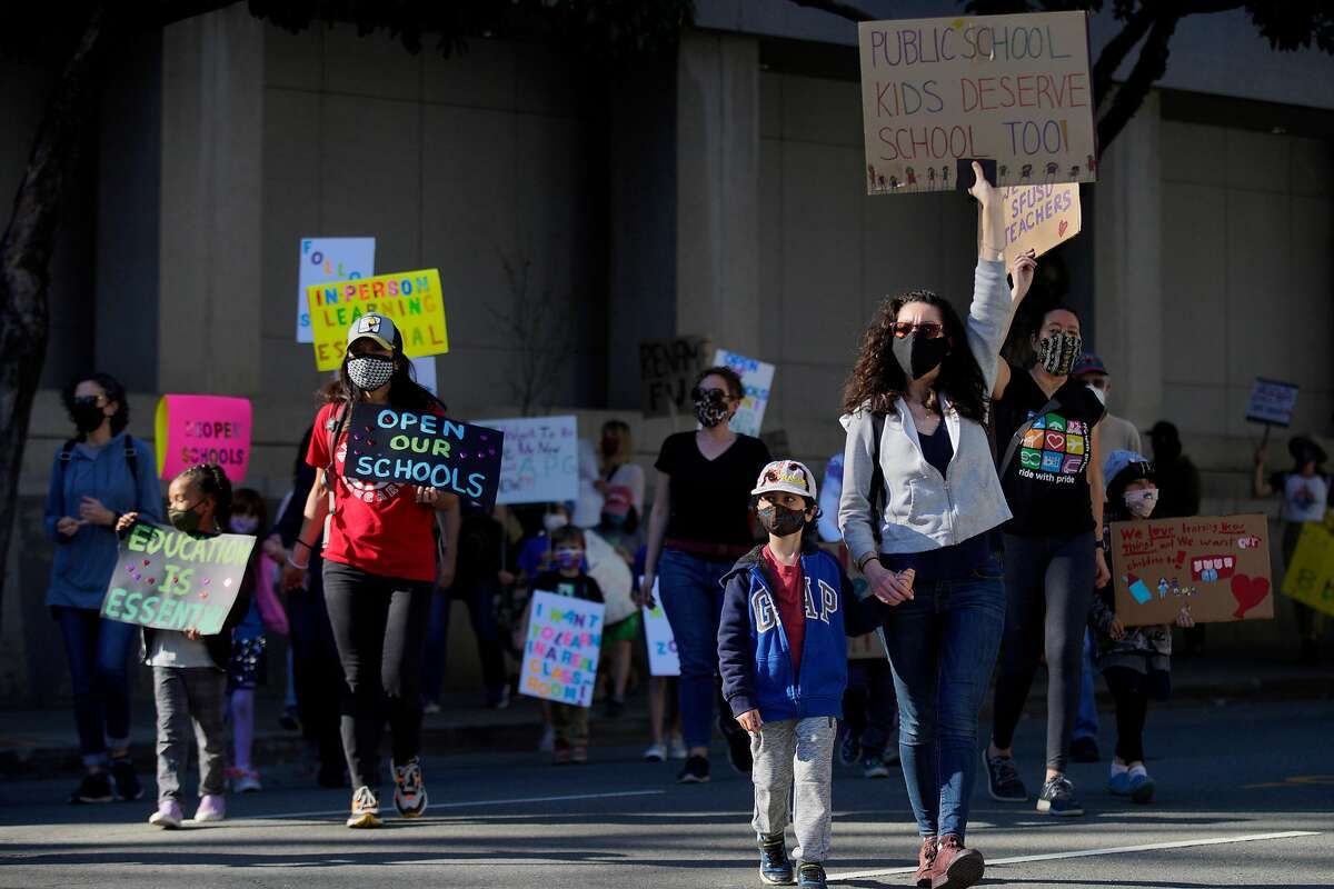 Hundreds of people march to City Hall after rallying outside the SFUSD building, Saturday, Feb. 6, 2021, in San Francisco, Calif. People protested against remote education and demanded schools to reopen in-person education.