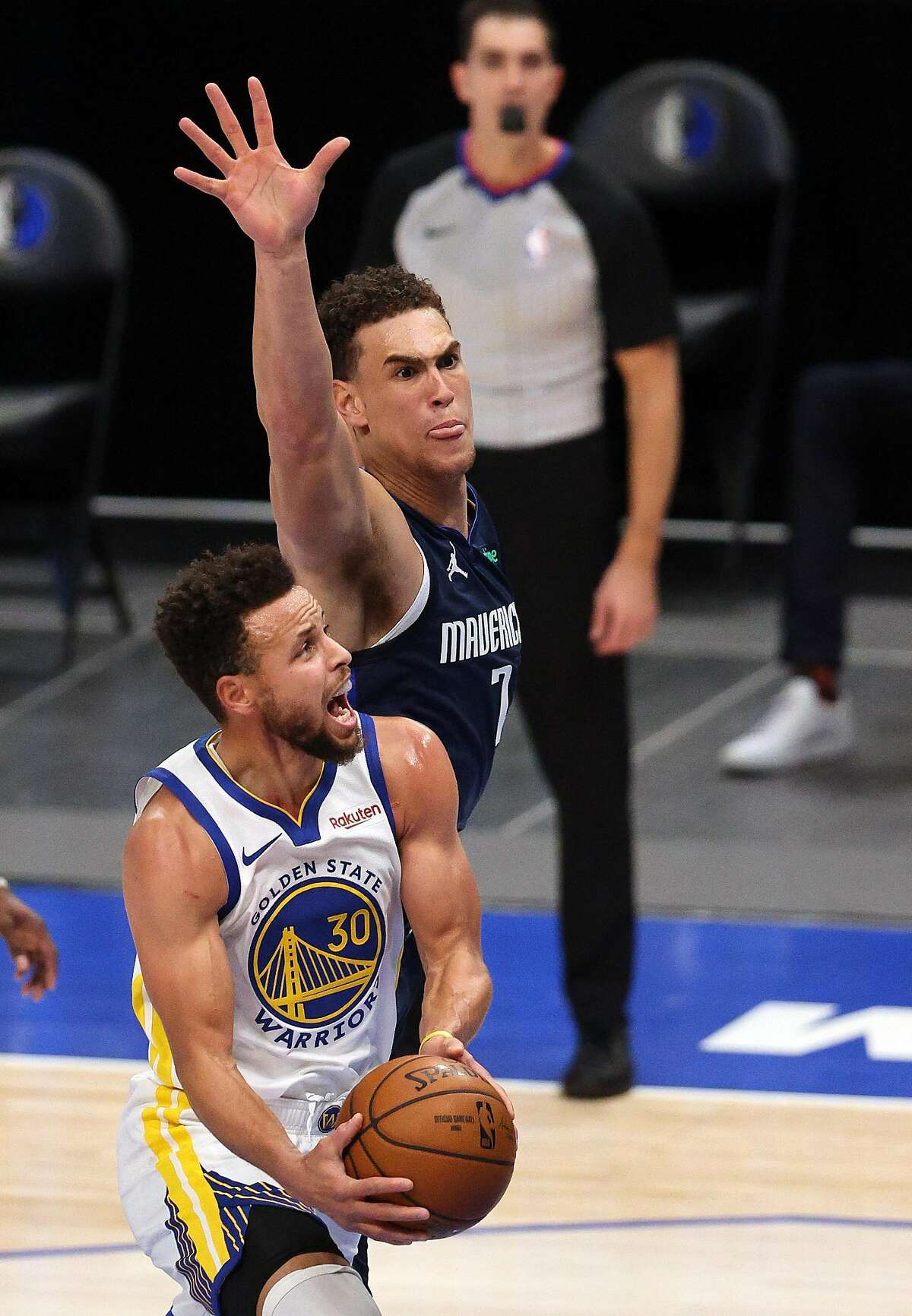 Stephen Curry maneuvers past the Mavericks' Dwight Powell in the second quarter. Curry made 11 3-point shots in the game.
