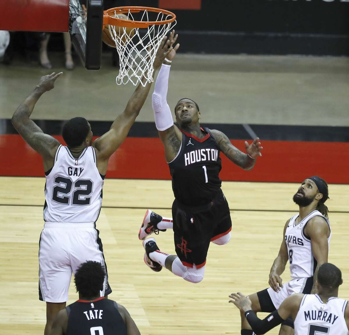 Houston Rockets guard John Wall (1) goes to the basket against San Antonio Spurs forward Rudy Gay (22) during the first half of an NBA basketball game at Toyota Center, in Houston, Saturday, Feb. 6.