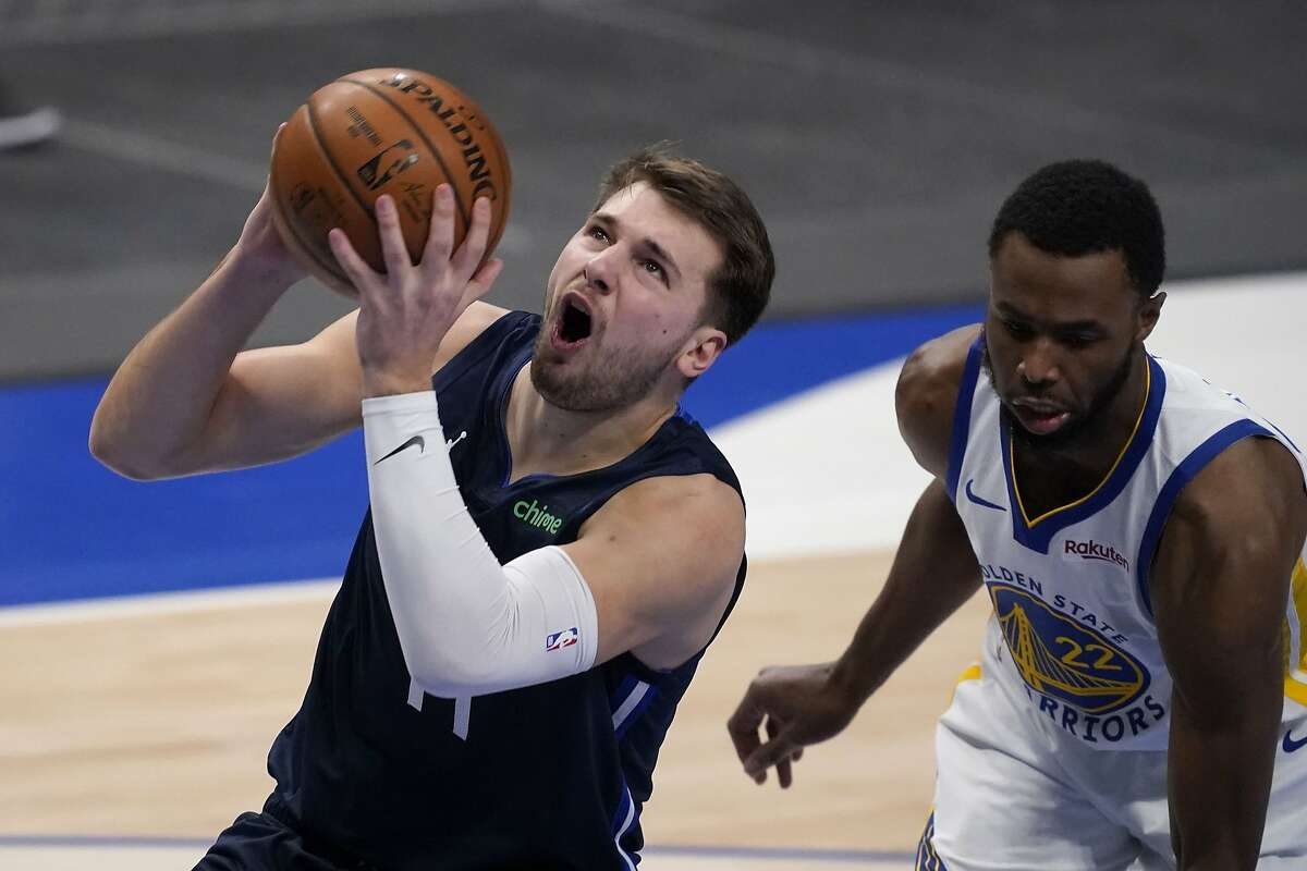 Dallas Mavericks' Luka Doncic (77) gets past Golden State Warriors' Andrew Wiggins (22) for a shot-attempt in the first half of an NBA basketball game in Dallas, Saturday, Feb. 6, 2021. (AP Photo/Tony Gutierrez)