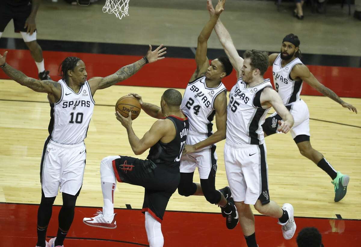 Houston Rockets guard Eric Gordon (10) drives to the basket against San Antonio Spurs forward DeMar DeRozan (10), guard Devin Vassell (24), and center Jakob Poeltl (25)during the first half of an NBA basketball game at Toyota Center, in Houston, Saturday, Feb. 6.