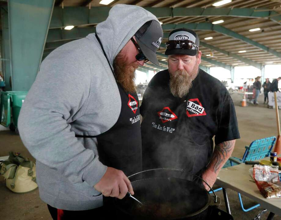 Russell Arnold, left, check his team's chili beside his brother, Richard, during the Montgomery County Fair Association's scholarship cook-off at the Montgomery County Fairgrounds on Saturday in Conroe. Photo: Jason Fochtman, Houston Chronicle / Staff Photographer / 2021 © Houston Chronicle