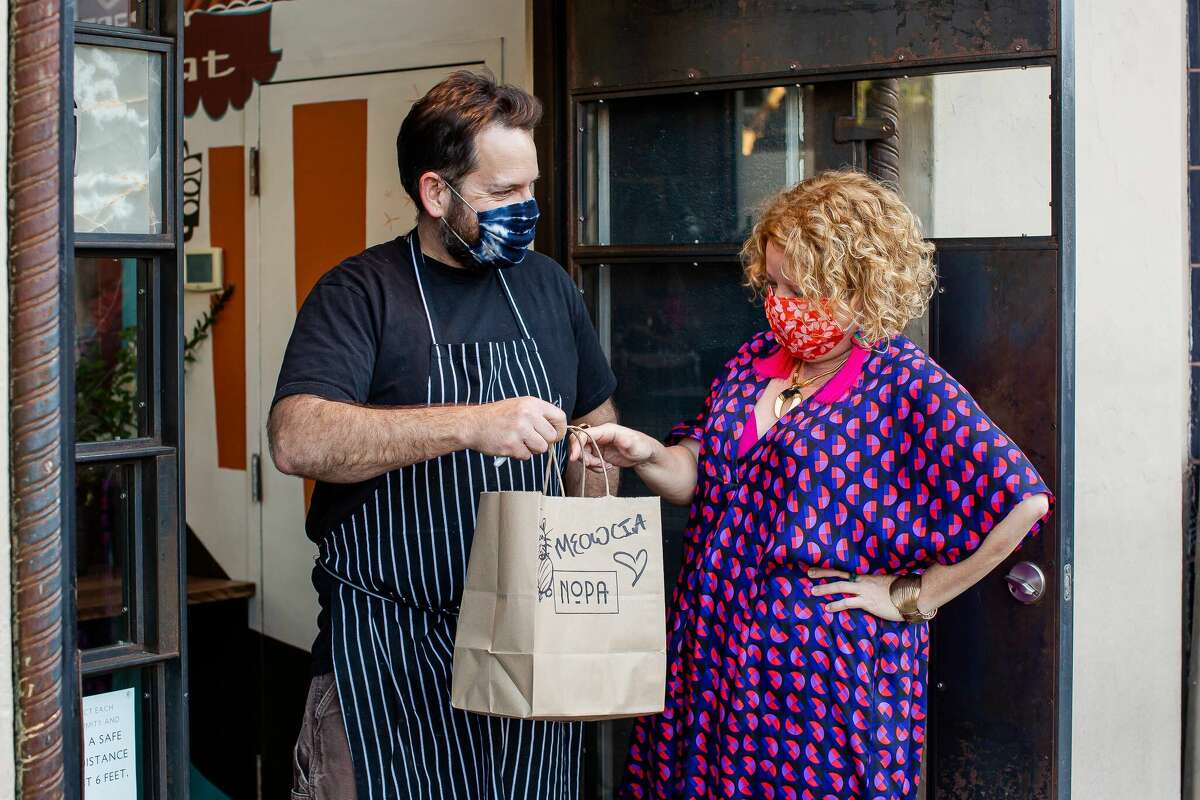 Marcia Gagliardi, right, poses with Nopa chef and co-owner Laurence Jossel with a bag of takeout. Gagliardi is celebrating 15 years of writing her food e-column, Tablehopper.