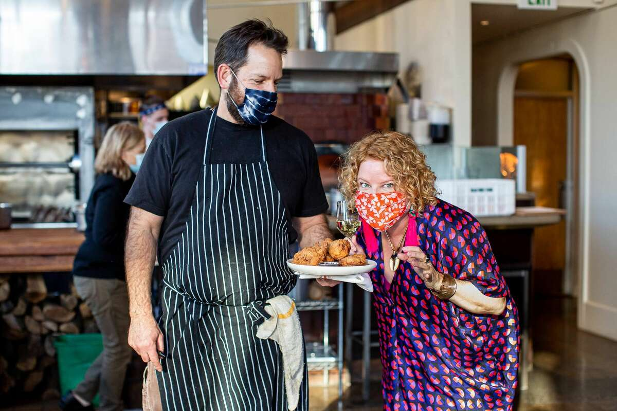 Marcia Gagliardi, right, poses with Nopa chef and co-owner Laurence Jossel over a plate of the restaurant's fried chicken. Gagliardiis celebrating 15 years of writing her food e-column, Tablehopper.