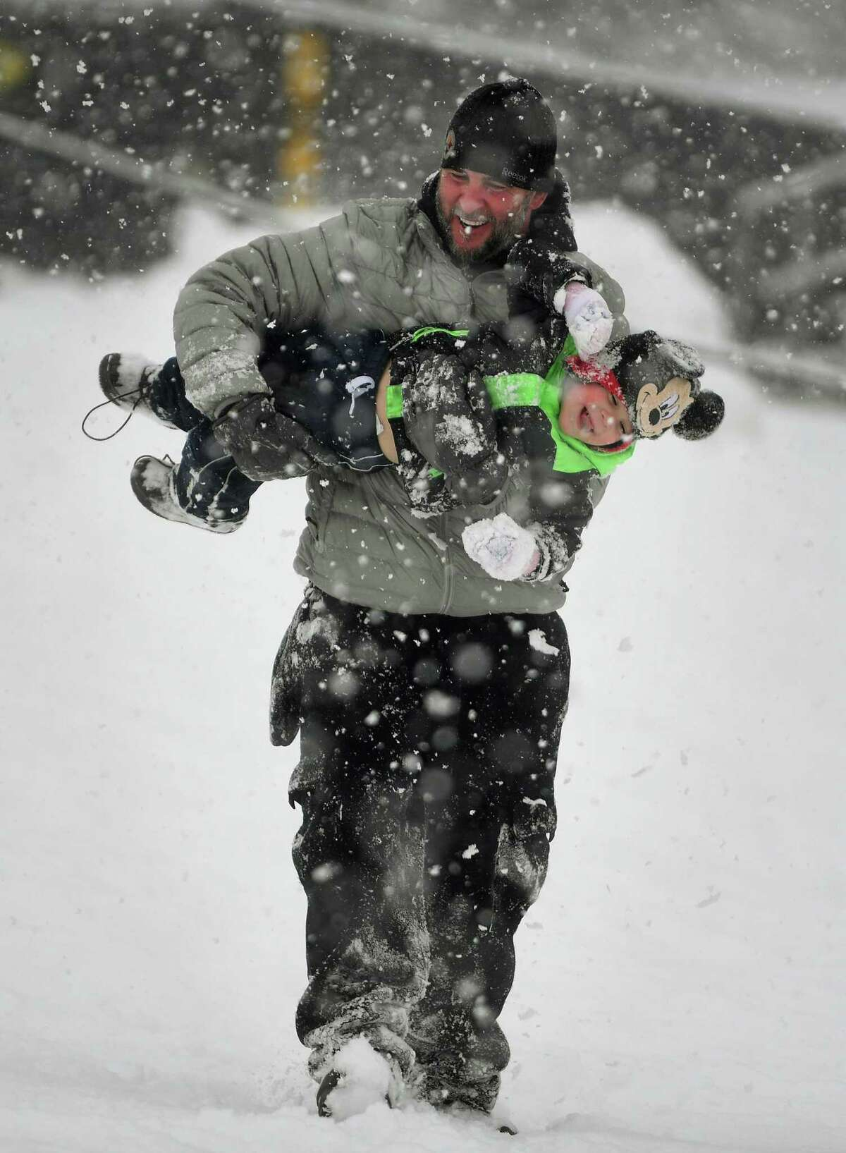 David Salerno and son Ethan, 2, of Milford, enjoy the snow during an afternoon of sledding at Jonathon Law High School in Miford, Conn. on Sunday, February 7, 2021.