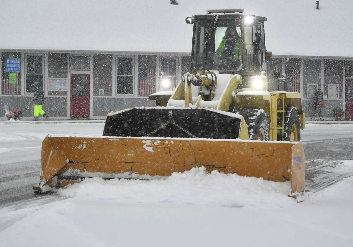 Workers clear snow during the height of the storm at the Stratford Train Station in Stratford, Conn. on Sunday, February 7, 2021.