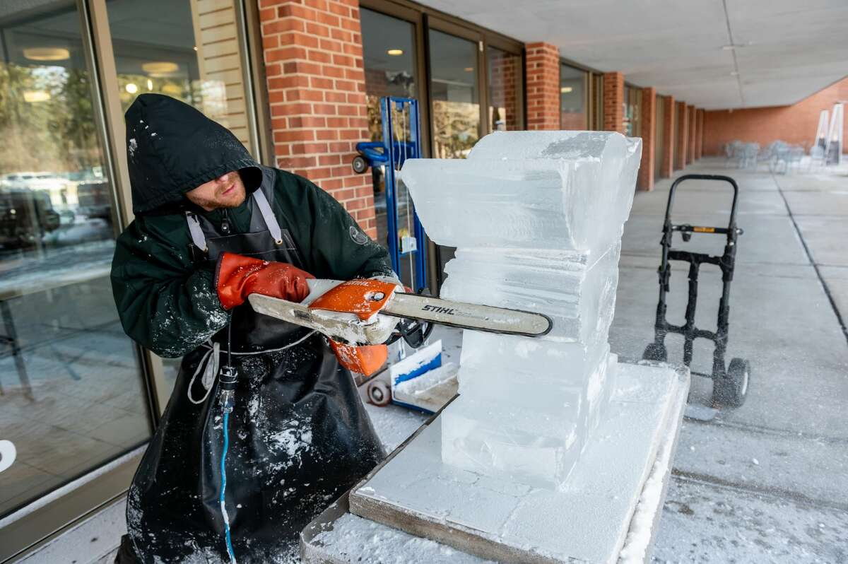 An Ice carver works on his design during the Winter Festival hosted by the Midland Center for the Arts Saturday, Feb. 6, 2021 in Midland. (Adam Ferman/for the Daily News)