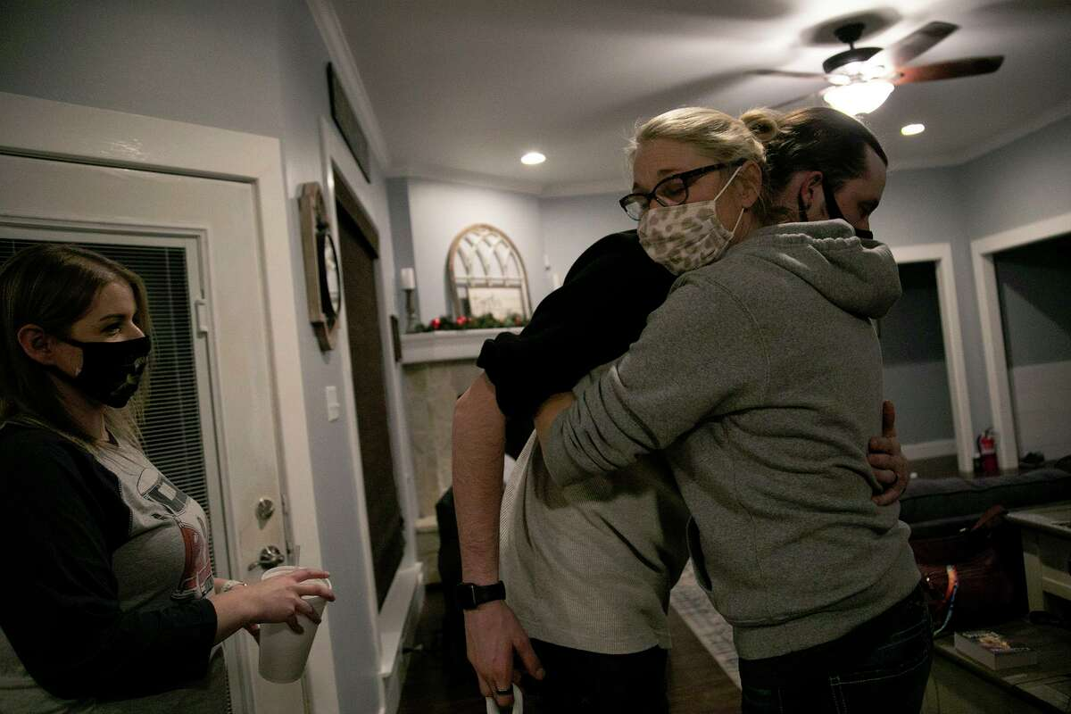 """Deona Jo """"DJ"""" Sutterfield hugs her son, Danny Sutterfield, as he leaves after dinner at their San Angelo home on Monday, Feb. 1, 2021. At left is Danny's wife, Whitney Sutterfield."""